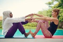 Женщины делая йогу poolside Стоковое Фото