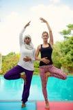 Женщины делая йогу poolside Стоковая Фотография