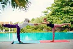 Женщины делая йогу poolside Стоковые Фото