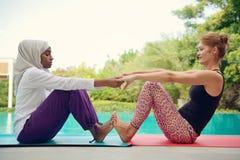 Женщины делая йогу poolside Стоковое фото RF