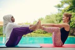 Женщины делая йогу poolside Стоковое Изображение RF