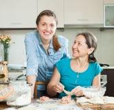 Женщины делая пироги или вареники мяса совместно Стоковое Фото