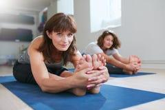Женщины делая представление йоги paschimottanasana Стоковая Фотография RF