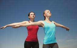 2 женщины делая представлять предпосылки голубого неба outdoorson йоги Стоковое Изображение