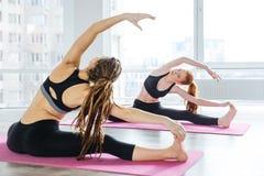 2 женщины делая протягивающ тренировки в центре йоги Стоковое Изображение RF