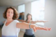 Женщины делая разминку йоги в классе Стоковая Фотография