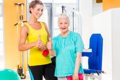 2 женщины делая спорт прочности в спортзале фитнеса Стоковая Фотография RF