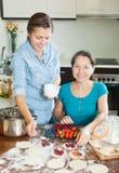 Женщины делая сладостное vareniki с ягодами Стоковое фото RF