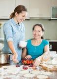 2 женщины делая сладостное vareniki с ягодами Стоковая Фотография