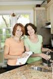 2 женщины делая тарелки в кухне Стоковые Изображения RF