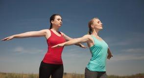 2 женщины делая фото йоги outdoors в природе Стоковые Изображения