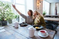 2 женщины делая фото selfie на smartphone Стоковое Изображение RF
