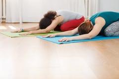 2 женщины делая asana йоги сидя в передней позиции загиба Стоковая Фотография