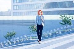 Женщины дела привлекательные идя вниз с улицы на предпосылке небоскреба Стоковое фото RF