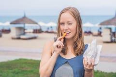Женщины едят зажаренные сладкие картофели в парке еда рыб огурца принципиальной схемы цыпленка сыра бургера предпосылки глубокая  Стоковое фото RF