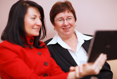2 женщины деля планшет Стоковое фото RF