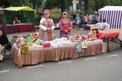Женщины (женщина) s в национальном сувенире торговлей костюма на дне города Стоковая Фотография RF