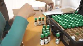 Женщины запах и пробуют ароматичное масло Руки принятые из бутылок случая медицинских Degustation видеоматериал