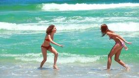 2 женщины играя совместно в море сток-видео