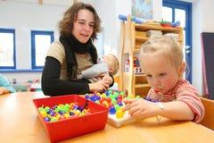Женщины играя с детьми в детском саде стоковая фотография
