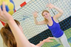 Женщины играя цель гандбола игры защищая стоковые изображения