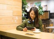 Женщины игры игры мобильный телефон однако стоковая фотография rf