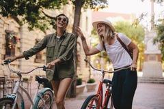 Женщины идя вниз с улицы города с их велосипедами Стоковые Изображения