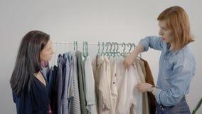 Женщины изучают одежды повиснули на вешалке Выбор шкафа очень важен для современных женщин видеоматериал