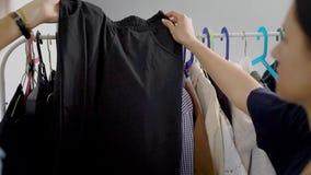 Женщины изучают одежды повиснули на вешалке Выбор шкафа очень важен для современных женщин акции видеоматериалы