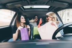 3 женщины имеют потеху в автомобиле после shoping и демонстрируют новые ботинки покупки Стоковые Изображения RF