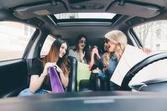 3 женщины имеют потеху и счастливого о покупках и новых ботинках в автомобиле Стоковая Фотография RF