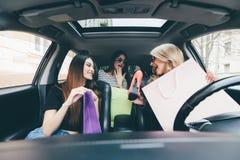 3 женщины имеют потеху и счастливого о покупках и новых ботинках в автомобиле Стоковое фото RF