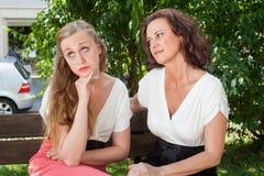 2 женщины имея аргумент на скамейке в парке Стоковое фото RF