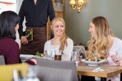 Женщины имея еду совместно на Coffeeshop Стоковое фото RF