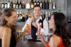 2 женщины имея коктеиль пока кельнер подготавливая коктеиль с шейкером коктеиля Стоковые Изображения RF