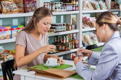 Женщины имея кофе в магазине Стоковые Изображения