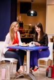 Женщины имея кофе и закуски на кофейне Стоковое Изображение