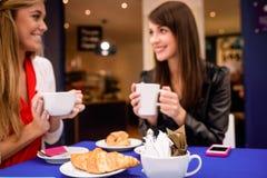 Женщины имея кофе и закуски на кофейне Стоковые Изображения RF