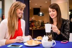 Женщины имея кофе и закуски на кофейне Стоковое Изображение RF