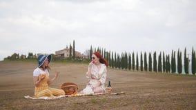 2 женщины имея пикник и есть плоды - Тоскану, дорогу кипарисов акции видеоматериалы
