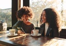 2 женщины имея потеху на кофейне Стоковые Изображения