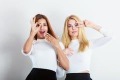 2 женщины имея потеху показывая знак с руками Стоковые Фотографии RF