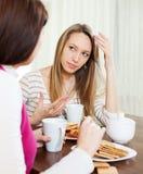2 женщины имея серьезный говорить на таблице Стоковые Изображения