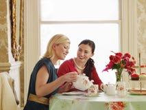 Женщины имея чай на обеденном столе стоковые изображения