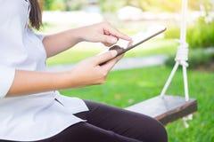 женщины используют таблетку для работы пока лежащ на sunbed в саде Стоковая Фотография RF