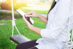 женщины используют таблетку для работы пока лежащ на sunbed в саде Стоковые Фото