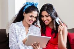 2 женщины используя ПК таблетки для онлайн оплаты Стоковая Фотография
