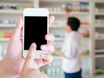 Женщины используя умный телефон в фармации запачкали предпосылку Стоковое Изображение RF