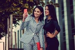 2 женщины используя smartphone Стоковое Изображение