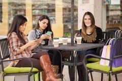 Женщины используя их smartphones на кафе Стоковые Изображения RF